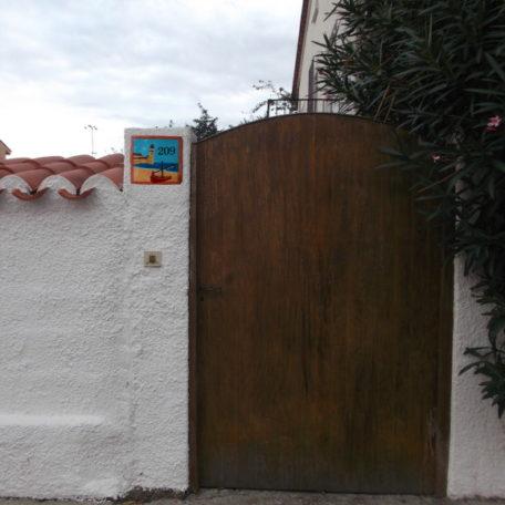 Plaque numéro de maison avec paysage marin et barque catalane verte, sur façade maison